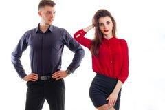 La jeune fille romantique dans un chemisier rouge et avec le rouge à lèvres sur des lèvres se tient près du haut type qui la rega Photographie stock libre de droits