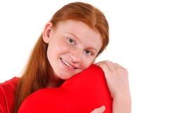 La jeune fille rouge de cheveux étreignent tendrement une forme de coeur sur le fond blanc Image stock
