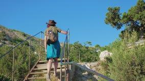 La jeune fille rousse de voyageur avec un chapeau de cowboy et un sac à dos monte des escaliers dans une zone montagneuse banque de vidéos