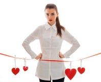 La jeune fille sérieuse dans la chemise blanche garde vos mains des côtés et se tient près d'un ruban rouge avec des coeurs Photographie stock libre de droits