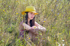 La jeune fille s'asseyant dans l'herbe, et au sujet de quelque chose pense Image libre de droits