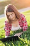 La jeune fille s'asseyant dehors sur l'herbe s'occupe de l'ordinateur portable, fonctionnement, regard songeur, un jour d'été deh Image stock