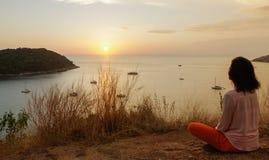 La jeune fille s'asseyant en position de méditation de lotus de yoga dans l'avant au bord de la mer sur les roches une observatio photo stock