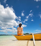 La jeune fille s'asseyent sur le bateau sur la plage blanche Images libres de droits