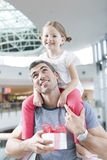 La jeune fille s'assied sur des épaules de pères Image libre de droits