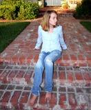 La jeune fille s'assied sur le porche Photos stock