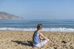 La jeune fille s'assied sur la plage image libre de droits