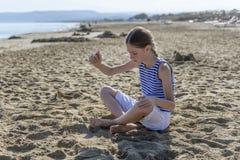 La jeune fille s'assied sur la plage photos libres de droits