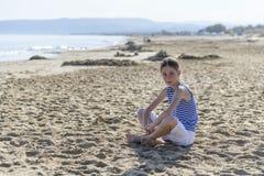 La jeune fille s'assied sur la plage images libres de droits