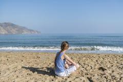 La jeune fille s'assied sur la plage photo libre de droits