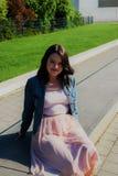 La jeune fille s'assied sur un fond de verdure photo libre de droits