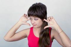 La jeune fille s'est arrêtée vers le haut de leurs oreilles Photo libre de droits