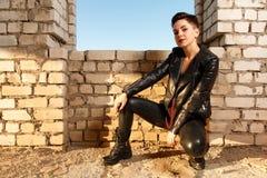 La jeune fille s'est habillée dans l'habillement en cuir, posant dans le buil abandonné Photographie stock
