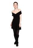 La jeune fille s'est habillée dans la robe noire occasionnelle et des espadrilles noires Photo stock