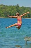 La jeune fille saute outre du dock Photographie stock