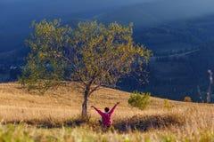 La jeune fille se lève ses mains tout en se reposant sous l'arbre sur le fond de montagne Photos stock