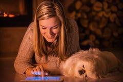 La jeune fille se repose avec un chien à la maison Image libre de droits