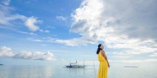 La jeune fille se tient sur la plage Photo libre de droits
