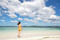 La jeune fille se tient sur la plage blanche Photos stock