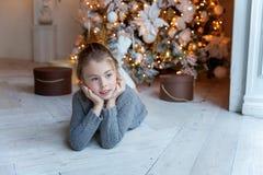 La jeune fille se trouve près d'un arbre de Noël Photo stock
