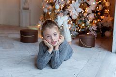 La jeune fille se trouve près d'un arbre de Noël Photos libres de droits