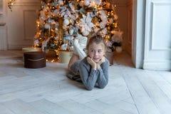 La jeune fille se trouve près d'un arbre de Noël Photographie stock