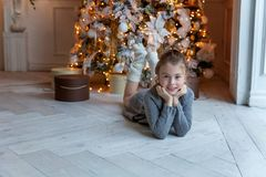 La jeune fille se trouve près d'un arbre de Noël Photographie stock libre de droits