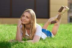 La jeune fille se trouve sur l'herbe verte Photographie stock