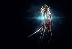 La jeune fille sexy se tient avec les épées Image stock