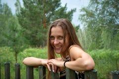 La jeune fille sourit à une barrière en bois Photo stock