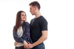 La jeune fille tendre souriant et regardant le type dans l'oeil est isolée sur un fond blanc Photographie stock
