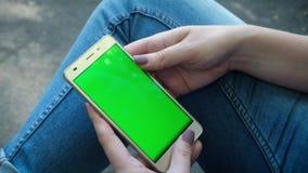 La jeune fille tient Smartphone avec l'écran vert au temps de soirée Mode de vie occasionnel banque de vidéos