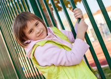 La jeune fille tient une barrière en métal Photos libres de droits