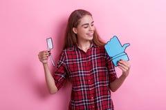 La jeune fille tient une brosse à dents de papier et un signe de rétroaction et regarde le signe photo stock