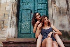 La jeune fille tresse ses cheveux du ` s de meilleur ami se reposant sur des escaliers dehors Femmes heureuses ayant l'amusement Images stock