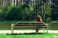 La jeune fille triste et s'asseyent sur un banc en bois en parc, elle a été déçue par l'amour doux Rêves de l'avenir Photographie stock