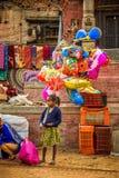 La jeune fille vend des ballons dans la rue de Katmandou Photographie stock libre de droits