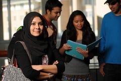 La jeune fixation arabe d'étudiant réserve dans le campus d'université Photo stock