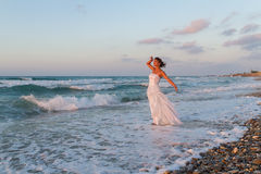 La jeune jeune mariée apprécie une promenade seule sur la plage au crépuscule Images libres de droits