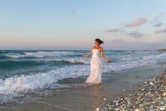 La jeune jeune mariée apprécie une promenade seule sur la plage au crépuscule Photos libres de droits
