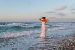 La jeune jeune mariée apprécie une promenade seule sur la plage au crépuscule Image libre de droits