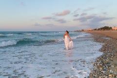La jeune jeune mariée apprécie une promenade seule sur la plage au crépuscule Image stock