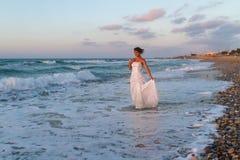 La jeune jeune mariée apprécie une promenade seule sur la plage au crépuscule Photos stock