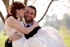 La jeune jeune mariée embrasse son marié Photo libre de droits