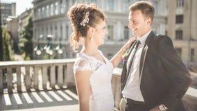 La jeune jeune mariée heureuse de couples de mariage rencontre le marié un jour du mariage Nouveaux mariés heureux sur la terrass Image libre de droits