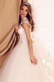 La jeune jeune mariée magnifique avec les cheveux bouclés blonds, utilise la robe de mariage et la couronne élégantes image libre de droits