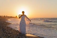 La jeune jeune mariée a plaisir à marcher sur une plage floue au crépuscule Photo stock