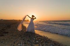 La jeune jeune mariée a plaisir à marcher sur une plage floue au crépuscule Image libre de droits
