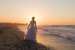La jeune jeune mariée a plaisir à marcher sur une plage floue au crépuscule Photographie stock