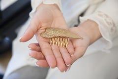 La jeune jeune mariée remet tenir un morceau de forme d'ornement de cheveux comme W d'or Photos stock